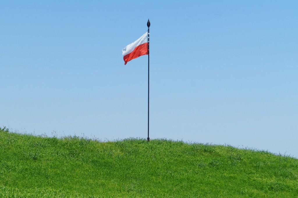 Polska flaga zatknięta na pozostałościach wału grodowego.