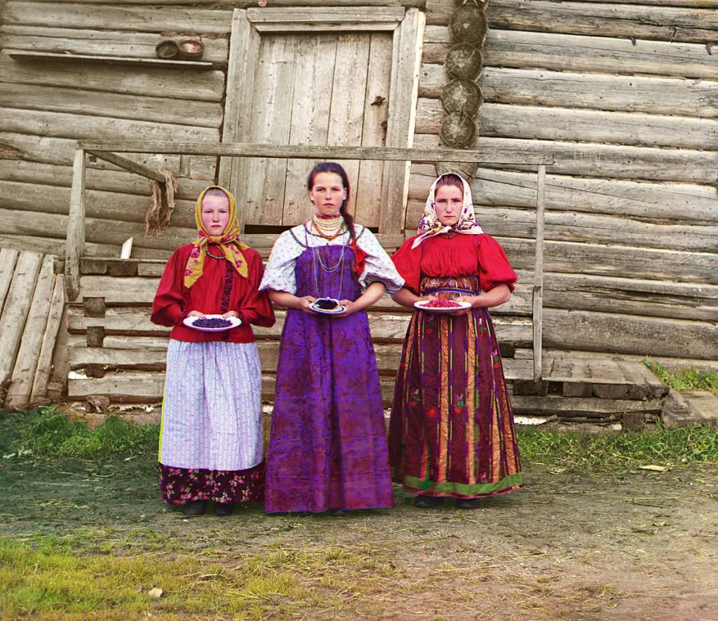 Trzy młode Rosjanki na tle tradycyjnego drewnianego domu. Rok 1909.