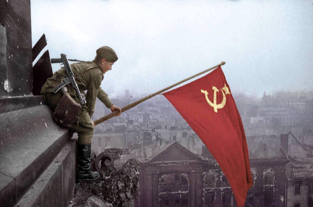 Żołnierz Armii Czerwonej zawiesza czerwony sztandar na gmachu Reichstagu, w tle ruiny pokonanego Berlina