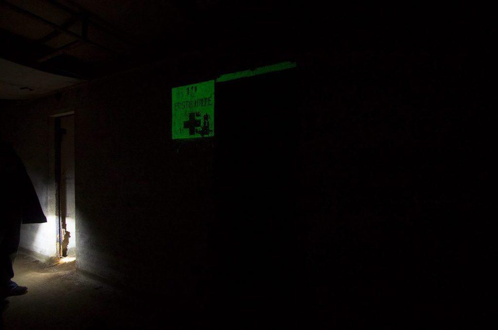 Punkt pierwszej pomocy w ciemności, napis pokryty farbą fluorescencyjną - Foto: Adrian Sitko