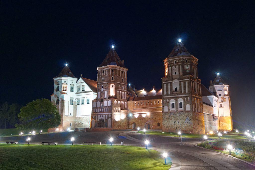 Zamek w Mirze w nocy jest pięknie oświetlony