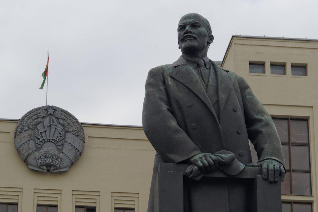 Lenin przed budynkiem parlamentu Republiki Białorusi, po lewej flaga i godło Białorusi (wzorowane na godle ZSRR)