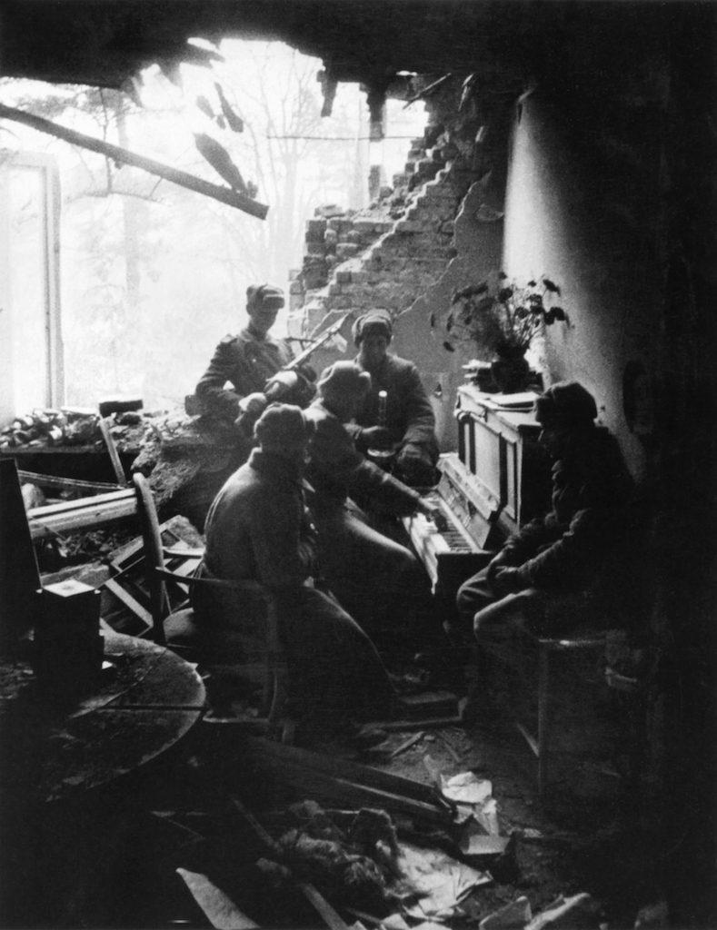 Żołnierz Armii Czerwonej gra na pianinie w jednym ze zrujnowanych domów