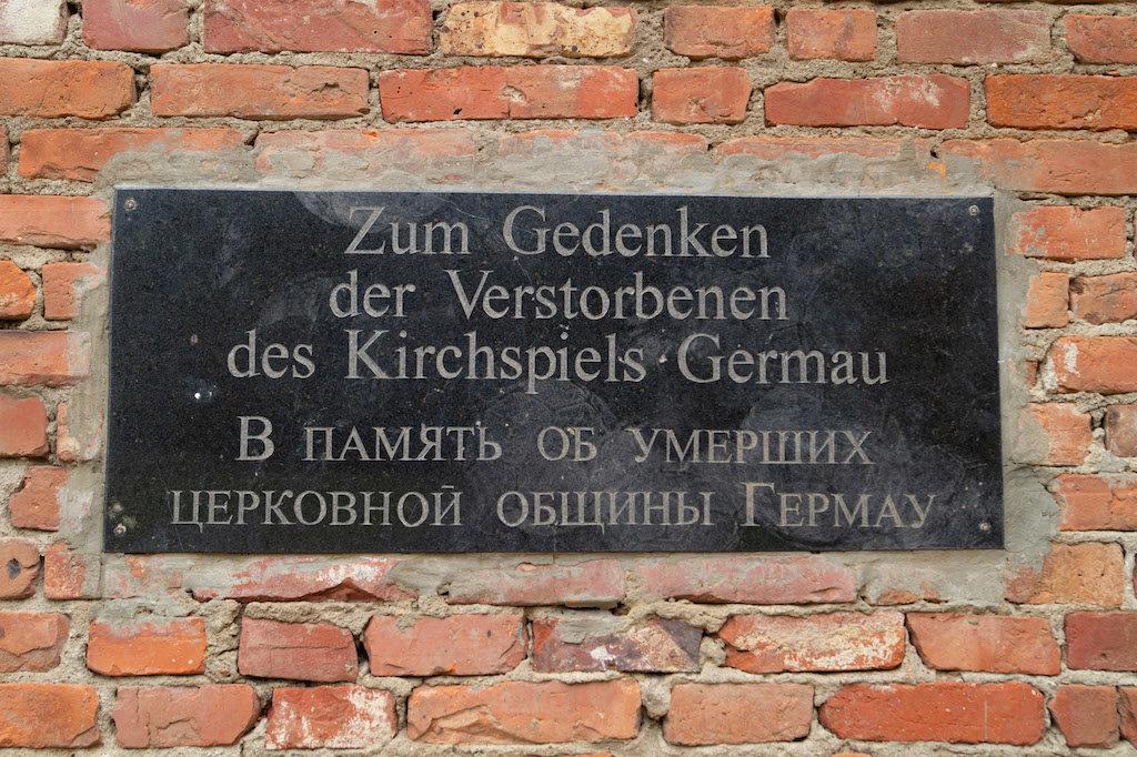 Płyta pamiątkowa na murze pozostałym po kościele w Russkoje