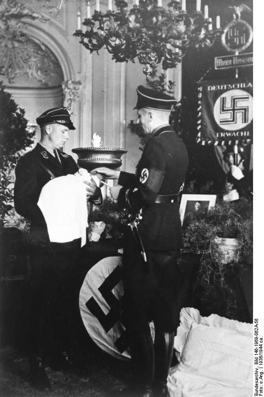 Chrzest dziecka z Lebensborn przed portretem Adolfa Hitlera – Źródło: Bundesarchiv