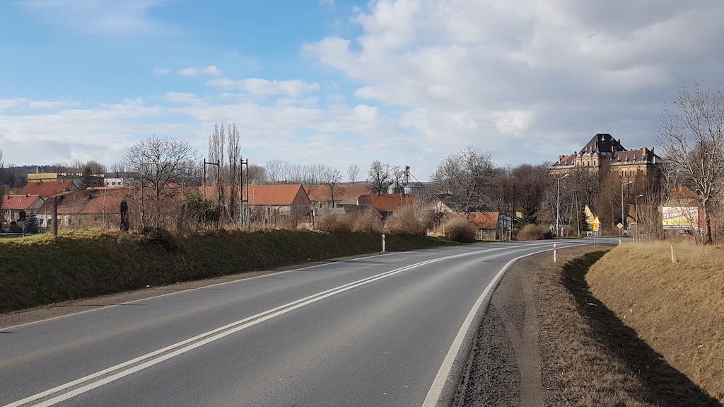 Ceglany gmach góruje nad wsią Mokrzeszów. Czy na tym zdjęciu widać pałac? Tak, ale nie tam, gdzie myślicie – jego prostokątna sylwetka maluje się na tle lasu z lewej strony kadru.