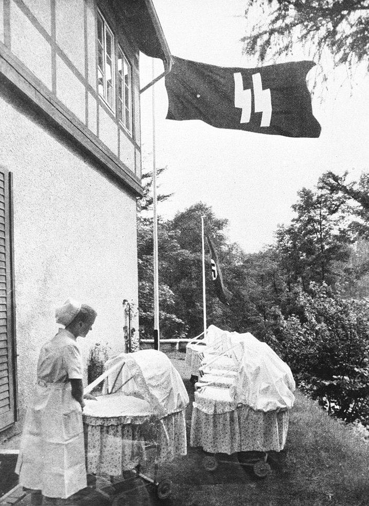 Pracująca w ośrodku Lebensborn pielęgniarka. W tle powiewające flagi – III Rzeszy oraz ozdobiona symbolem SS – Źródło: Bundesarchiv