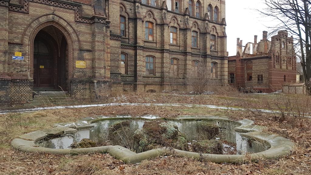 Postarajmy się przy tym nie wpaść do fontanny – gmaszysko przyciąga wzrok, ale pod nogi patrzeć trzeba. Ruiny z prawej strony kadru pokazują, jak może skończyć główny budynek szpitala, jeśli nikt nie zadba o jego przyszłość.