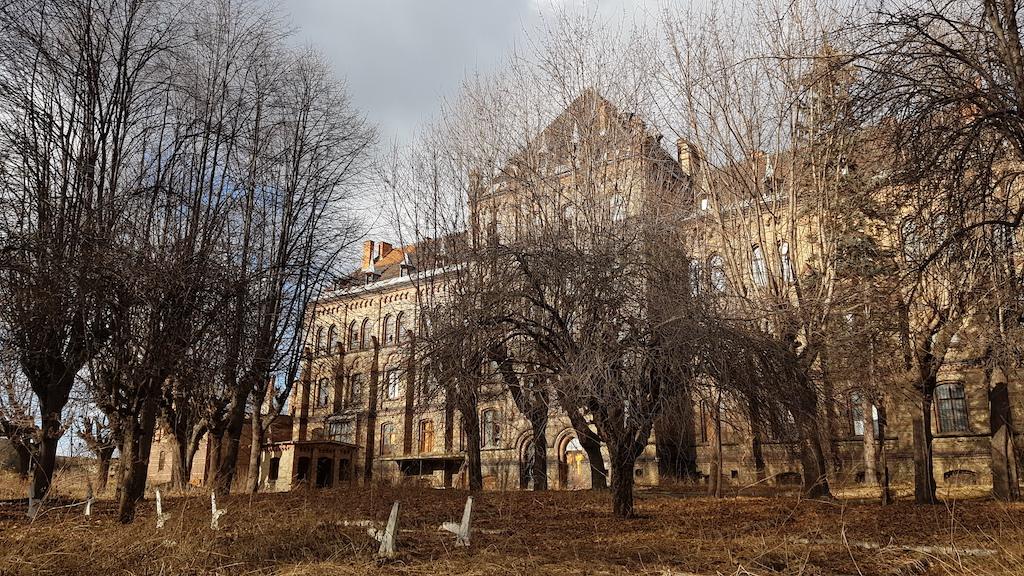 Mokrzeszowski szpital widoczny od południa. Ku tylnemu wejściu prowadzi wysadzana drzewami aleja – niegdyś zapewne licznie odwiedzana przez pacjentów, gdy pogoda sprzyjała spacerom.