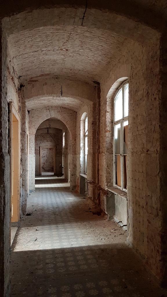 """Jak widać, nie wszędzie korytarze zachowały """"cywilizowany"""" wygląd. Nie licząc obudów ciężkich pieców znajdujących się w piwnicach kotłowni, wszelkie elementy żelazne, jak grzejniki i rury, wywędrowały ze szpitala dawno temu. Pozwala to spojrzeć na przestrzał budynku w górę lub dół przez otwory, którymi niegdyś rury przebiegały. Instalacje elektryczne spotkał los identyczny."""